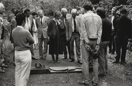 Photograph of people gathered around a sleeper, possibly at the launch of sculpture Iron Road