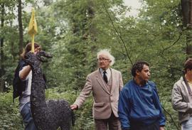 Photograph of Zadok Ben-David in blue jacket with part of sculpture As There Is No Hunting Tomorrow