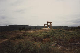 Photograph of figure walking towards Place/ Giant's Chair with landscape in background